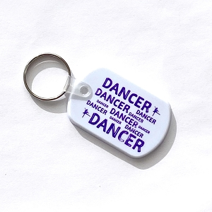 Share your love for dance with this durable silicone rubber keychain with DANCER and arabesque ballerinas imprinted in purple.