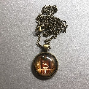 This vintage inspired necklace features a beautiful vignette of a dancing ballerina encased in a cabochon pendant. The antique brass pendant is suspended from an antique brass chain that is fastened with a lobster clasp.