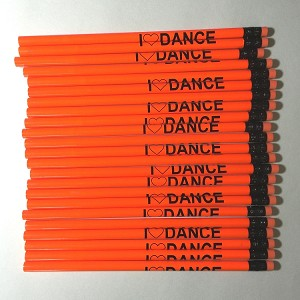 Each neon orange pencil displays the word, I [heart] DANCE, wrapped around it.